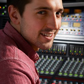 Male sitting in a recording studio mixing tracks