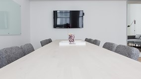 Empty board room with a white table, black chairs and a TV screen